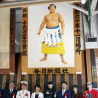 Three-time Olympic women's wrestling gold medalist Saori Yoshida (second from right) and others pose under a portrait of former yokozuna Chiyonofuji at JR Ryogoku station in Sumida Ward. | POOL / VIA KYODO
