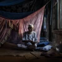 A Rohingya Muslim man reads the Koran at one of the few undamaged mosques in northern Rakhine state, Myanmar, in 2019.  | ADAM DEAN/THE NEW YORK TIMES