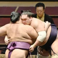 Terunofuji grapples with Asanoyama during the July Grand Sumo Tournament on Aug. 3 in Tokyo. | KYODO