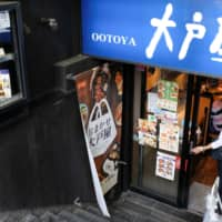 A patron enters a restaurant run by fast-food dining chain Ootoya in Tokyo on Monday. Having succeeded in a hostile takeover bid, competitor Colowide as said it plans to immediately send new directors to Ootoya after an extraordinary shareholders' meeting. | REUTERS