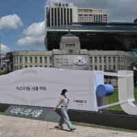 A woman walks past a mask-shaped sculpture in front of Seoul City Hall in Seoul on Friday.  | AFP-JIJI