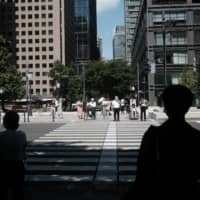 People wait to cross an intersection in Tokyo's Marunouchi business district in August. | BLOOMBERG