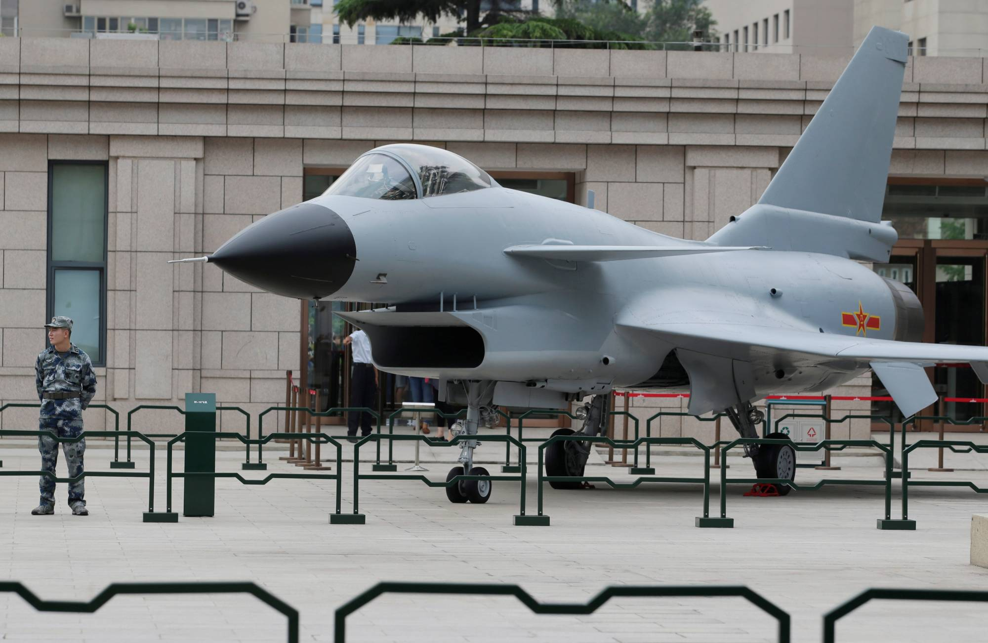 A soldier stands next to a J-10 fighter jet during an exhibition outside the Military Museum of the Chinese People's Revolution in Beijing. | REUTERS