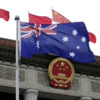 The Australian flag flutters in front of the Great Hall of the People in Beijing. | REUTERS
