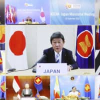 Foreign Minister Toshimitsu Motegi (center) and his counterparts from ASEAN, China and South Korea attend a videoconference Wednesday. | POOL / VIA KYODO
