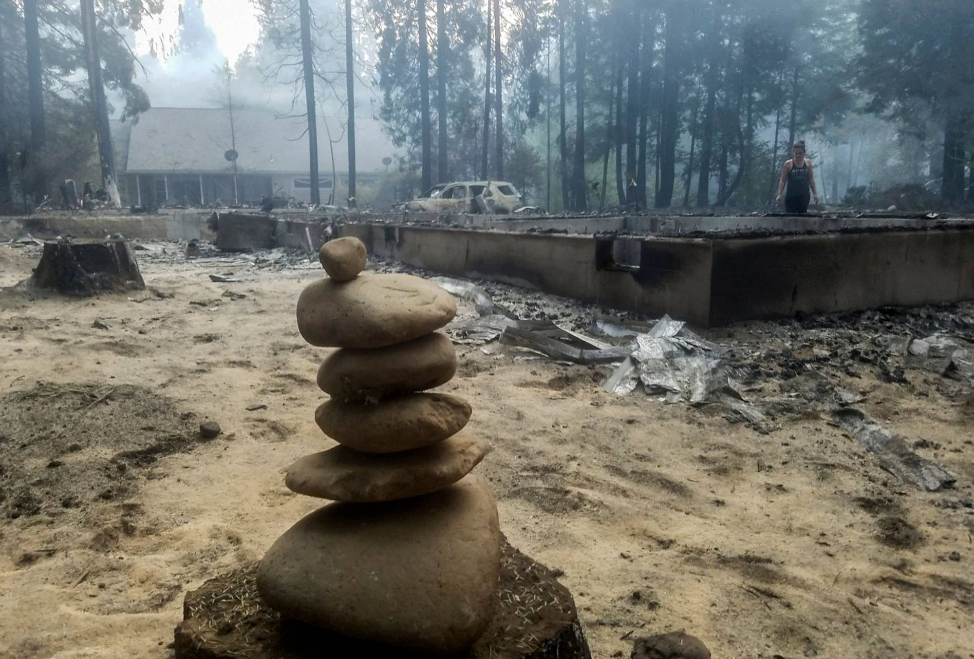 A woman walks near the foundation of a burned out house after the passing of the Holiday Farm fire in McKenzie Bridge, Oregon, on Wednesday.    AFP-JIJI