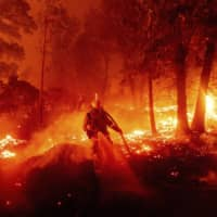 A firefighter battles the Creek Fire as it threatens homes in the Cascadel Woods neighborhood of Madera County, California, on Monday. | AP