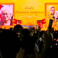 Images of historian Somsak Jeamteerasakul and former diplomat Pavin Chachavalpongpun are projected onto a giant screen at Thammasat University during a demonstration in Bangkok in August. The banner reads 'To your highest majesty with rice, BBQ pork and soup. Long live the king.' | REUTERS
