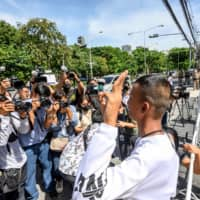 Pro-democracy protester Panupong Jadnok (also known as Mike Rayong), who was recently released from Thai prison, poses for the media at a rally outside the Embassy of Japan in Bangkok on Tuesday, during a small demonstration to thank Tokyo for giving refuge to Pavin Chachavalpongpun. | AFP-JIJI