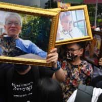Protesters hold pictures of government critics Somsak Jeamteerasakul (left) and Pavin Chachavalpongpun, who are living in self-imposed exile, at a pro-democracy protest in Bangkok in August.  | AFP-JIJI