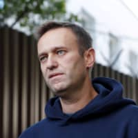 Russian opposition leader Alexei Navalny speaks with journalists after he was released from a detention center in Moscow last August.  | REUTERS