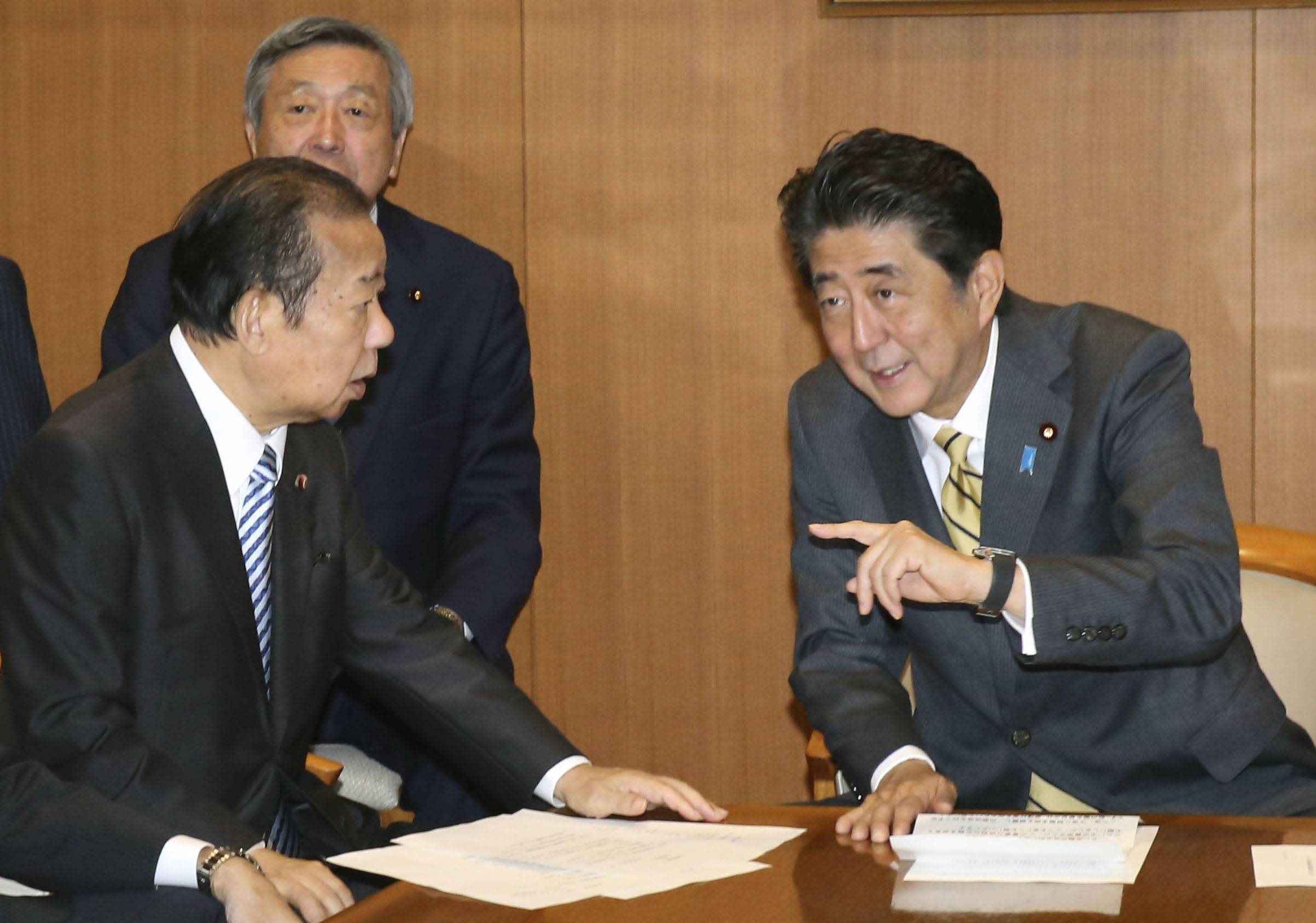 Prime Minister Shinzo Abe speaks with Toshihiro Nikai, LDP secretary-general, at party headquarters in Tokyo after a leadership shake-up on Sept. 11, 2019. | KYODO