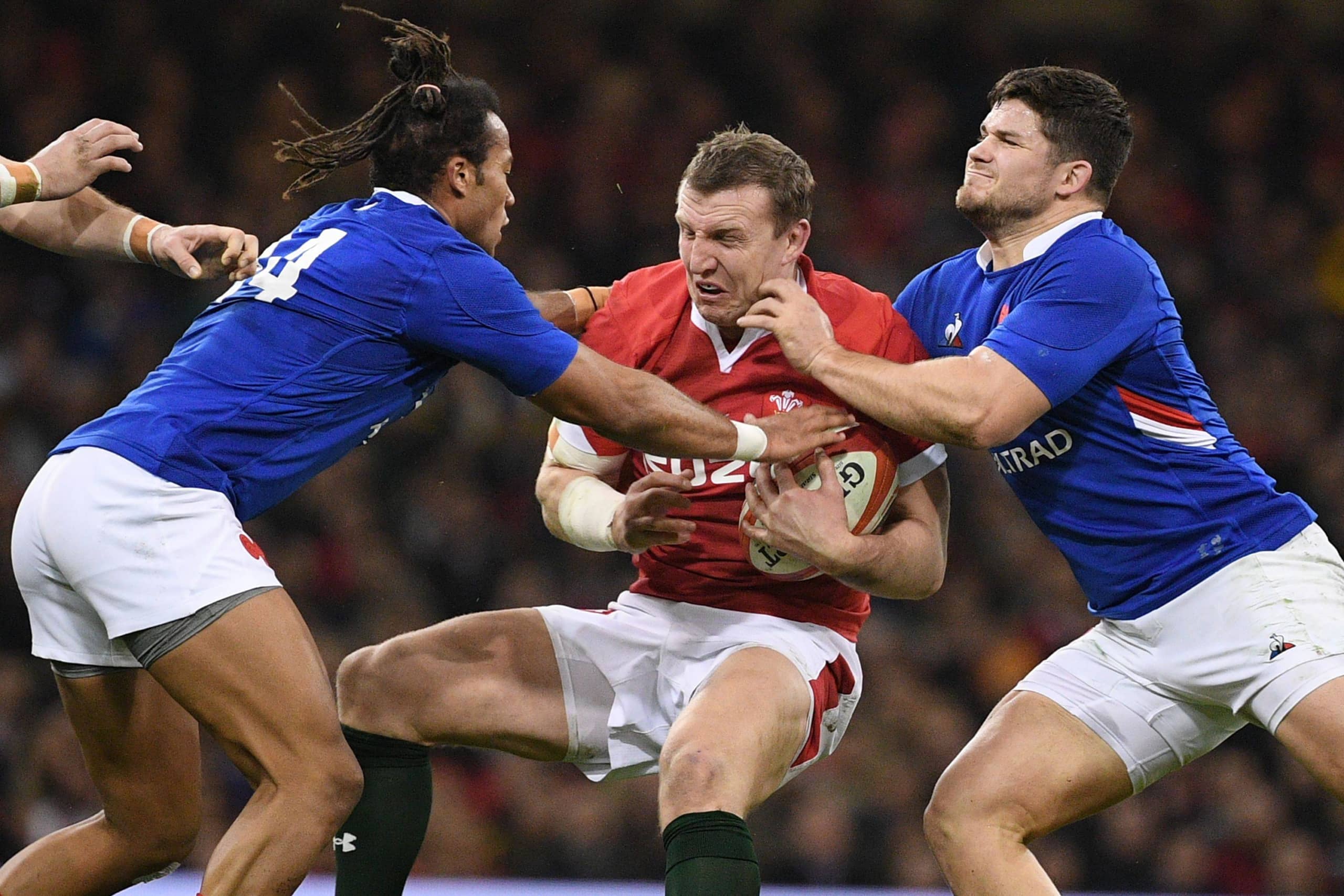 Wales center Hadleigh Parkes (center) is tackled during a Six Nations match between Wales and France on Feb. 22 in Cardiff. | AFP-JIJI