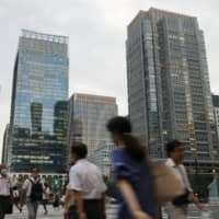 People walk in Tokyo's Marunouchi business district on Aug. 17. | KYODO