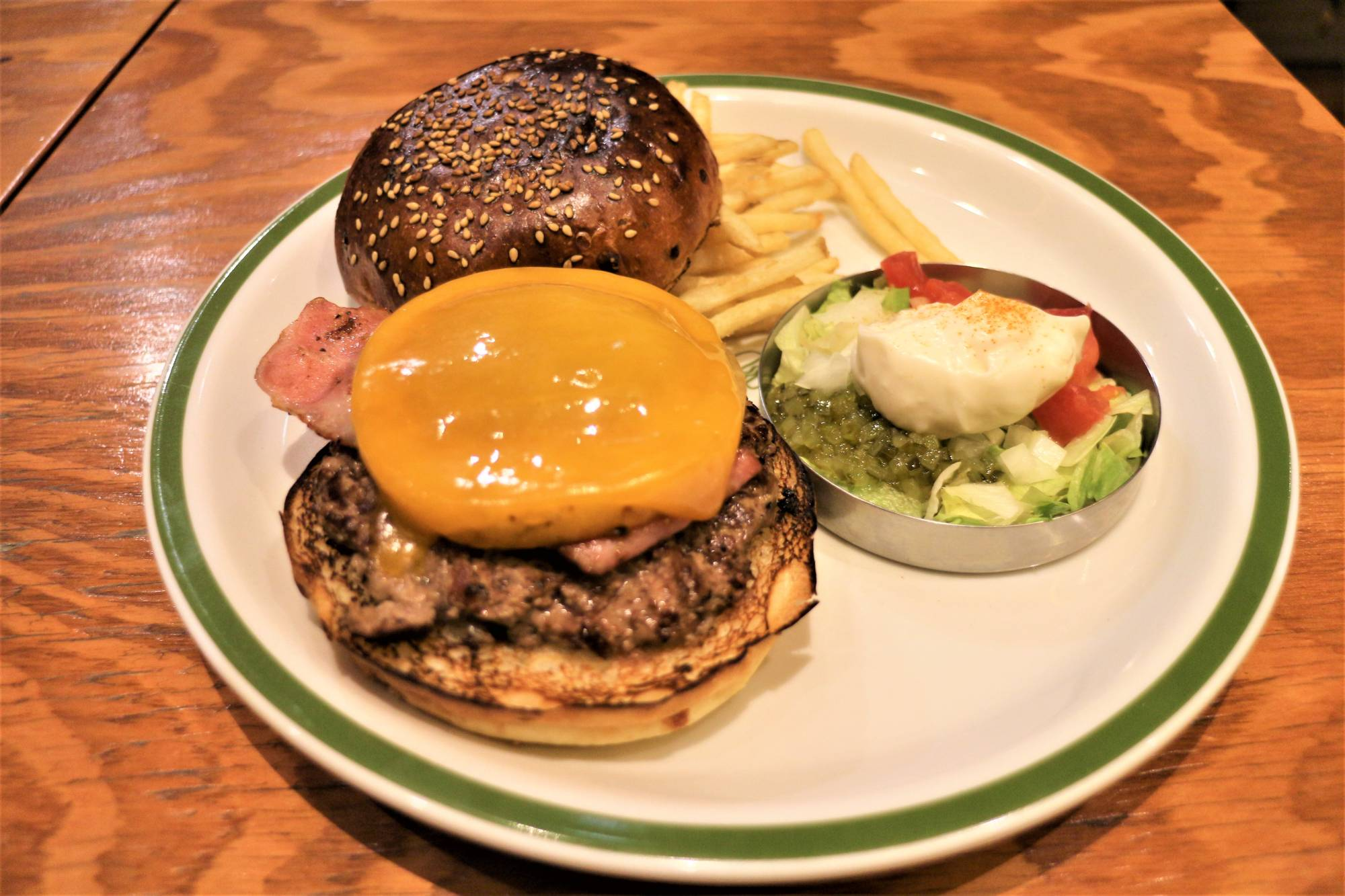 The Shop Burger (¥1,450) at The Burger Shop comes topped with pineapple, half-melted cheese, grated onion and barbecue sauce, plus a side salad. | HARUKA MURAYAMA