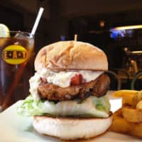 EAT Grill and Bar's knockout Balentien Burger (¥1,150) is spiced with Cajun seasoning and comes topped with tartar sauce and tomato salsa. | COURTESY OF EAT GRILL AND BAR