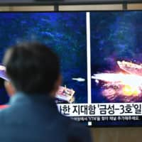 A man watches a television news broadcast showing file footage of a North Korean missile test at a railway station in Seoul on April 14. | AFP-JIJI