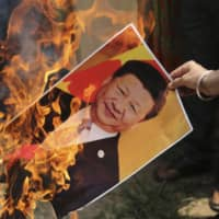 A Bharatiya Janata Party activist burns a photograph of Chinese President Xi Jinping during a protest in Jammu, India, in July. A bitter military standoff between India and China has pushed New Delhi closer to the U.S., Australia and Japan. | AP