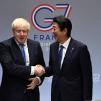 British Prime Minister Boris Johnson meets with Prime Minister Shinzo Abe at the Group of Seven summit in Biarritz, France, in August last year. | POOL / VIA REUTERS