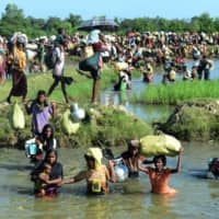 Rohingya refugees walk through a shallow canal in October 2017 after crossing the Naf River in Palongkhali near Ukhia, as they flee violence in Myanmar to reach Bangladesh. | AFP-JIJI