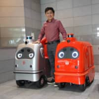 Hisashi Taniguchi, CEO of ZMP Inc., stands with the service robots his company has produced at its headquarters in Bunkyo Ward. | ALEX MARTIN