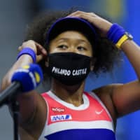 Naomi Osaka adjusts her mask after defeating Jennifer Brady in their U.S. Open semifinal on Thursday in New York. | AP
