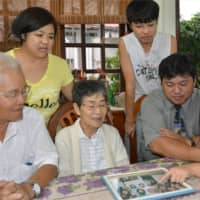 People of Japanese descent look at family photos in Piedade, Brazil, in March 2014. The vast majority of young people belonging to the Japanese diaspora around the world want to make connections with Nikkei in other countries, a survey has shown. | KYODO