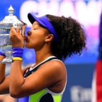 Naomi Osaka kisses the U.S. Open trophy after defeating Victoria Azarenka on Sunday in New York. | USA TODAY / VIA REUTERS
