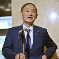 Chief Cabinet Secretary Yoshihide Suga speaks to reporters in Tokyo Sunday after appearing on an NHK TV program. | KYODO