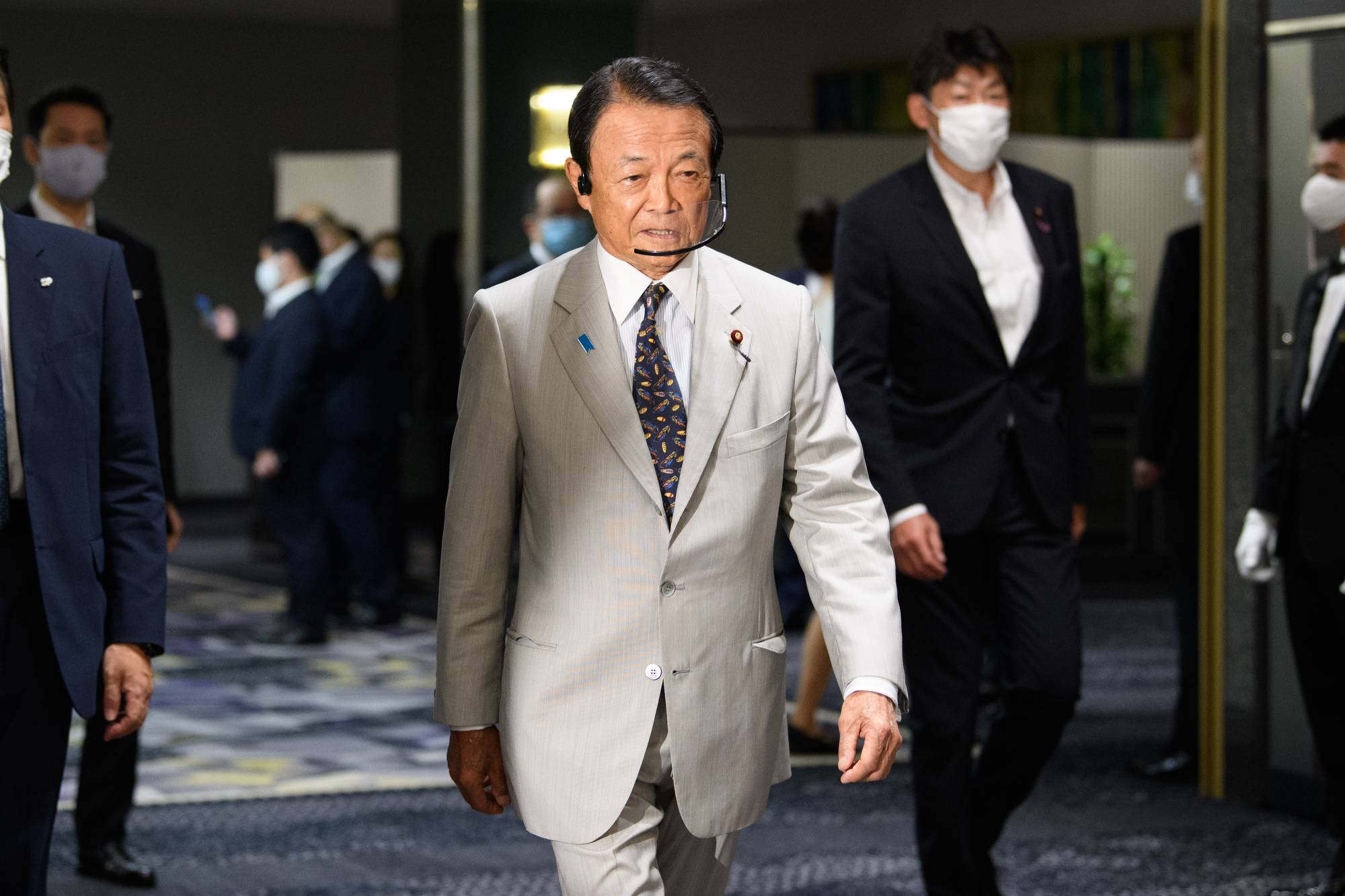Deputy Prime Minister Taro Aso arrives for a ceremony marking the beginning of Chief Cabinet Secretary Yoshihide Suga's campaign for the Liberal Democratic Party leadership race in Tokyo on Tuesday. | BLOOMBERG