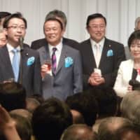 President of the House of Councilors Akiko Santo poses with Finance Minister Taro Aso following the merger of their LDP factions in 2015.   KYODO