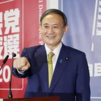 Yoshihide Suga poses for photos prior to his first news conference as the new president of the Liberal Democratic Party at party headquarters in Tokyo on Monday. | KYODO