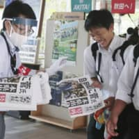 Newspapers are handed out Monday to people in Akita Prefecture, the hometown of Yoshihide Suga who was elected the new president of the Liberal Democratic Party earlier in the day. | KYODO