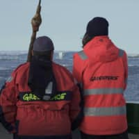 Crew members look at the first piece of ice they spotted on an expedition aboard the Arctic Sunrise. | REUTERS