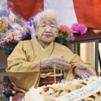 Kane Tanaka, recognized as the world's oldest living person by Guinness World Records, receives a birthday cake for her 117th birthday at a nursing home in the city of Fukuoka in January. Japan's centenarians surpassed 80,000 for the first time this year, government data shows. | KYODO