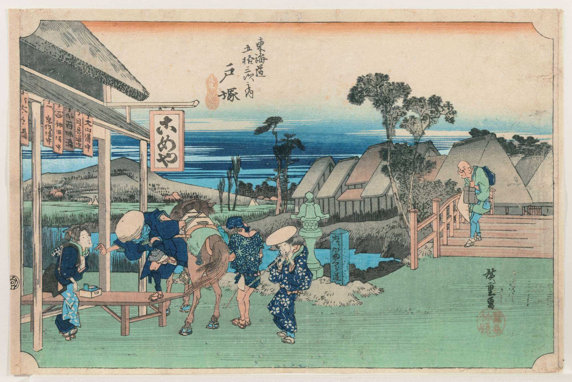 'Fifty-Three Stations of the Tokaido Road: Totsuka (Motomachi Detour),' Hoeido edition, by Utagawa Hiroshige I (circa 1833-34). The scenery along the Tokaido road spreads out beyond the eaves of the teahouse. A traveler appears to leap from his horse. Hiroshige's placement of his figures shows careful thought: two men with faces hidden flanking the horse, two women with faces visible to their right and left, and, farther back to the right, a lone old man approaching from the bridge. | YAMATANE MUSEUM OF ART