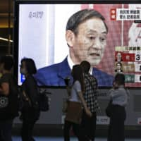 News of Yoshihide Suga's landslide win in the Liberal Democratic Party presidential election is broadcast on a monitor in Osaka on Monday. | KYODO