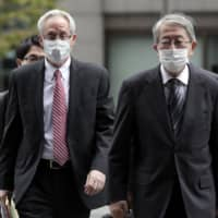 Former Nissan Motor Co. executive Greg Kelly (left) arrives for the first hearing of his trial at the Tokyo District Court in Tokyo on Tuesday. | POOL / VIA AP
