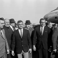 Allan Kuhn, fourth from left, and Jack 'Murph the Surf' Murphy, sixth from left, suspects in the heist of the Star of India sapphire and Star Ruby of Burma from New York's Museum of Natural History, at Kennedy Airport after their arrest in Florida in 1964.   PATRICK BURNS / THE NEW YORK TIMES