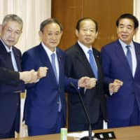 New LDP executives pose for photos at the party's general council meeting on Tuesday. | KYODO