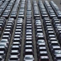 New vehicles await export from a port in Yokohama in February. | BLOOMBERG