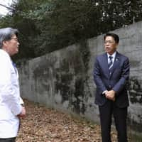 Officials speak outside the National Sanatorium Kikuchi Keifuen in Koshi, Kumamoto Prefecture, in January. | KYODO