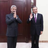 Indian External Affairs Minister Subrahmanyam Jaishankar (left) and Chinese Foreign Minister Wang Yi pose for a photo as they meet in Moscow last Thursday.  | XINHUA / VIA AP