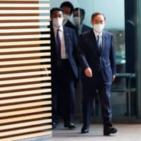 Yoshihide Suga enters the prime minister's official residence in Tokyo on Wednesday. Given that Suga is still a relatively unknown quantity, some in the political and diplomatic community fret whether he will be able to maintain political stability after Shinzo Abe's record-breaking tenure.  | REUTERS