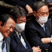 Remarks by Cabinet ministers, including Finance Minister Taro Aso (left), have added fuel to speculation about an early election. | REUTERS