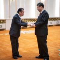 Liberal Democratic Party Secretary-General Toshihiro Nikai shakes hands with Chinese leader Xi Jinping before a meeting at the Great Hall of the People in Beijing in April last year. | POOL / VIA REUTERS