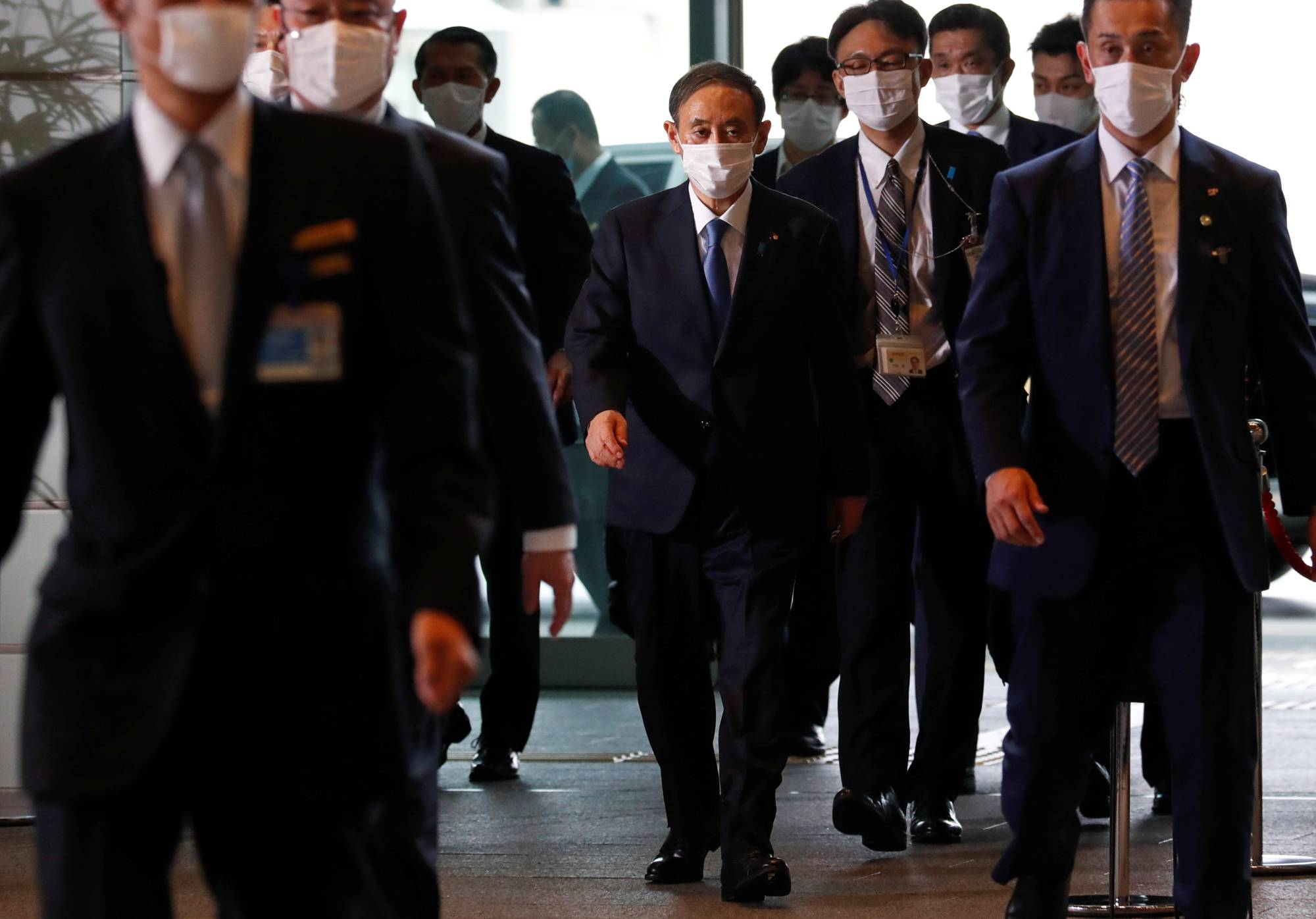 Newly elected Prime Minister Yoshihide Suga arrives at the Prime Minister's Office in Tokyo on Wednesday. | REUTERS