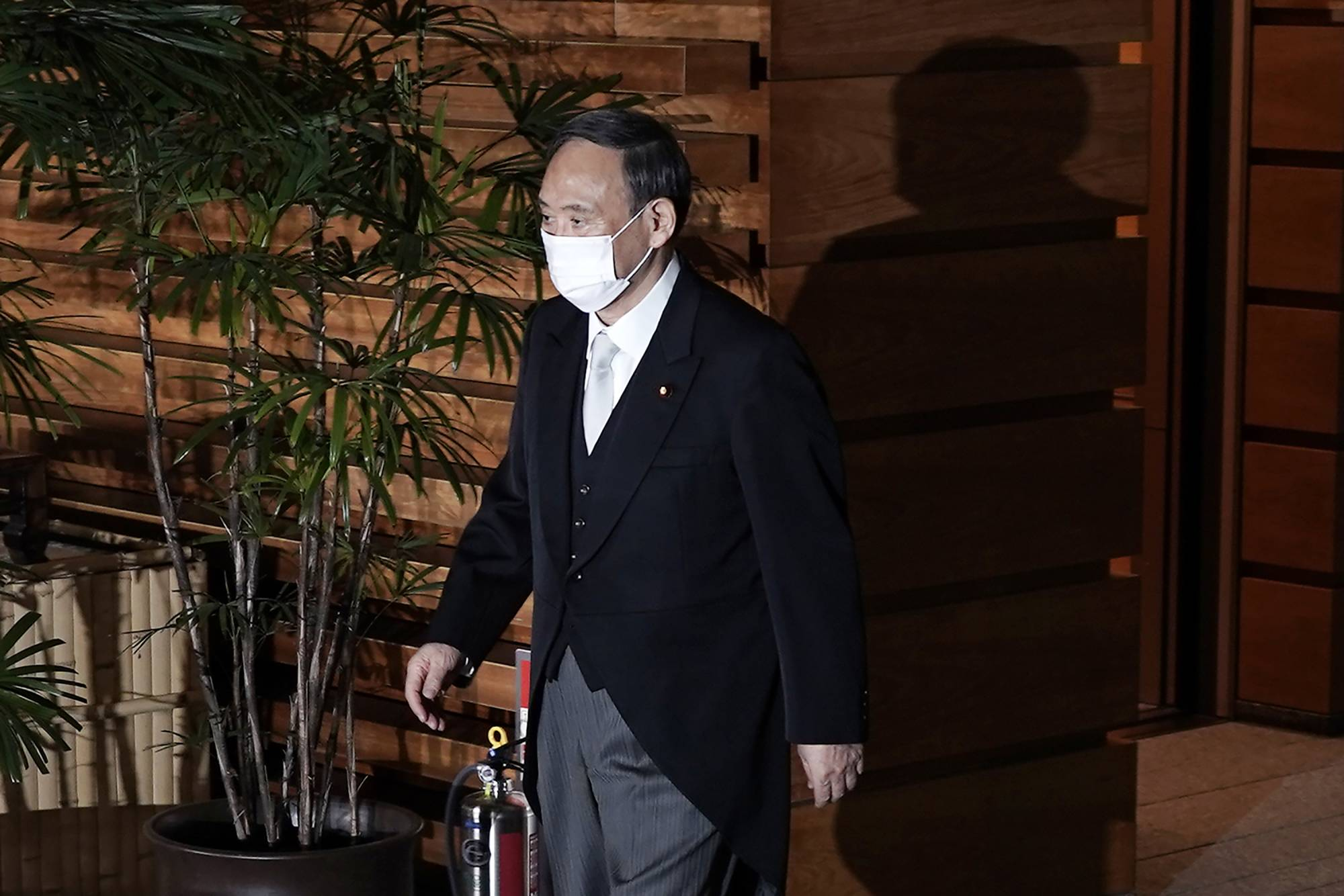 Yoshihide Suga leaves his official residence for the Imperial Palace to attend the attestation ceremony of his new Cabinet on Wednesday in Tokyo. | AP