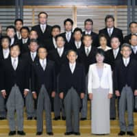 Newly elected Prime Minister Yoshihide Suga (center, front row) and his Cabinet pose for a photo at the Imperial Palace in Tokyo on Wednesday. | POOL / VIA KYODO