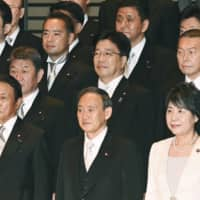 Newly elected Prime Minister Yoshihide Suga (center) and members of his Cabinet pose for a photo at the Imperial Palace in Tokyo on Wednesday. | POOL / VIA KYODO